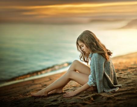 坐在海滩上的小女孩图片