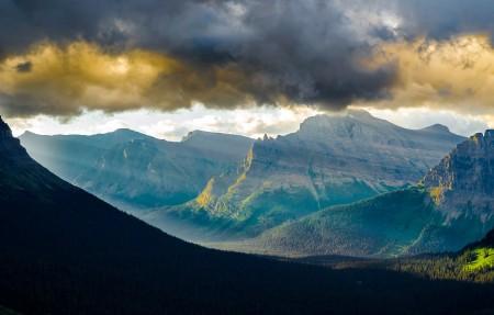 蒙大拿州冰川国家公园的洛根山脉 早晨与太阳穿过山谷和云层4K超高清壁纸精选